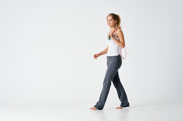 Sportvrouw trainen met springtouw fitness lichte achtergrond