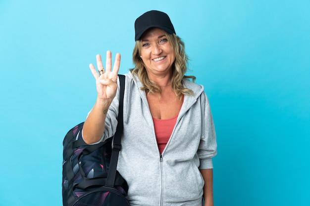 Sportvrouw van middelbare leeftijd over geïsoleerde achtergrond gelukkig en vier tellen met vingers