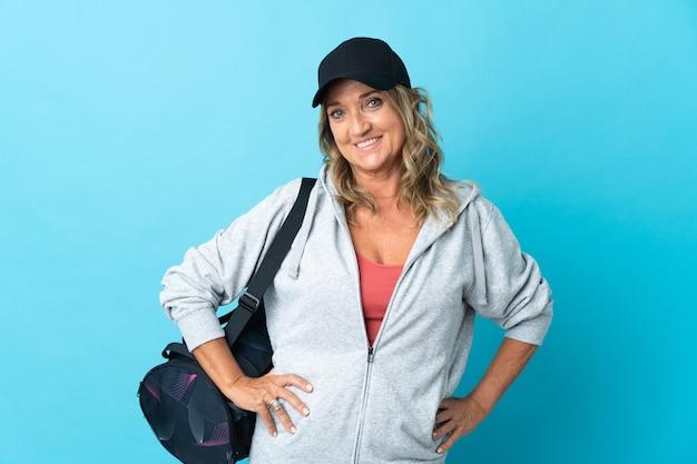 Sportvrouw van middelbare leeftijd over geïsoleerde achtergrond poseren met armen op heup en glimlachen