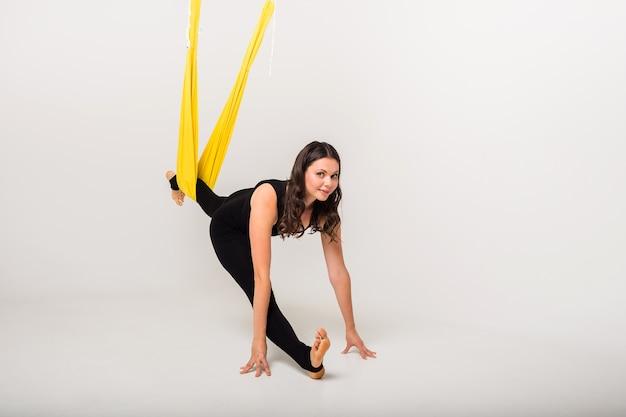 Sportvrouw voert rekoefeningen uit met een hangmat op een witte muur