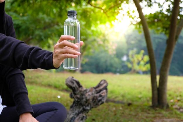 Sportvrouw wat water drinken uit een fles na de training.