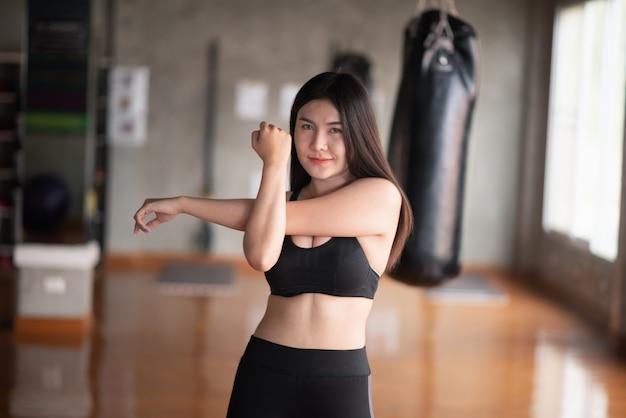 Sportvrouwen die zich vóór oefening in de gymnastiek uitrekken