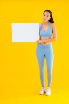 Sportwear toont de portret mooie jonge aziatische vrouw sportwear leeg wit aanplakbord op geel