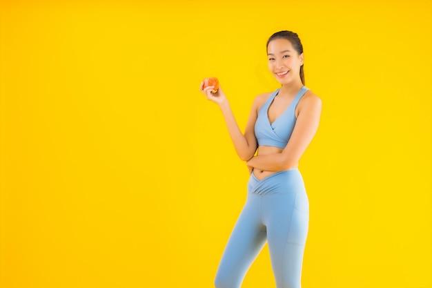 Sportwear van de portret mooie jonge aziatische vrouw sportwear klaar voor oefening op geel