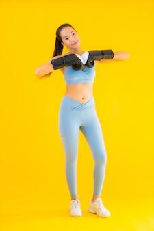Sportwear van de portret mooie jonge aziatische vrouw sportwear op geel