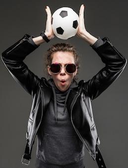 Sportweddenschap concept. verrast stijlvolle meisje in een leren jas en een grijze sweater met bril houdt de bal boven haar hoofd op een donkergrijze achtergrond