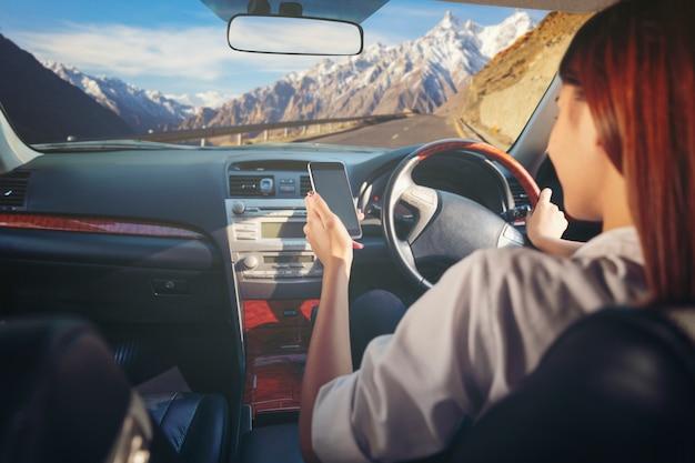 Spot omhoog van vrouw die telefoon met behulp van terwijl het drijven achter het wiel op de weg.