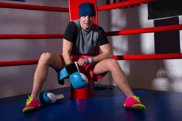 Spotive jonge mannelijke bokser zit in de buurt van de rode hoek van een gewone boksring