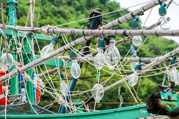 Spotlights hingen aan een vissersboot en vissen op inktvis om 's nachts vis te vangen