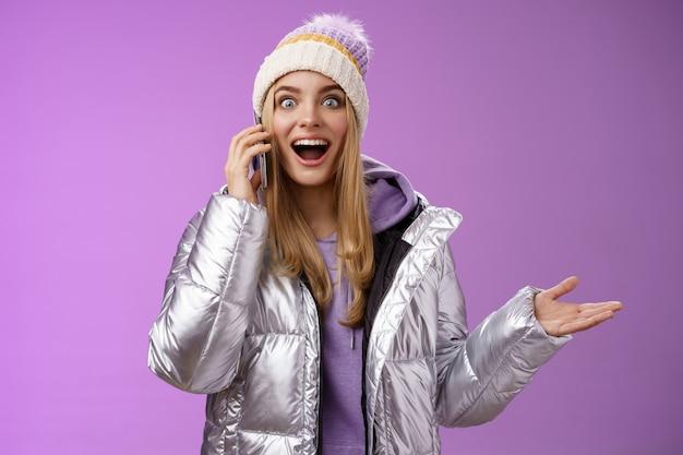 Spraakzaam geamuseerd blond meisje geweldig goed nieuws horen hand opsteken verrast blij praten smartphone verbreden ogen tevreden perfecte informatie, permanent verbaasd blij paarse achtergrond.