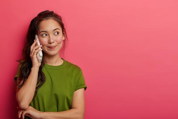Spraakzaam tienermeisje besteedt uren praten via smartphone, houdt mobiele telefoon dicht bij oor, roept vrienden, geniet van een leuk gesprek, kijkt met doordachte uitdrukking opzij, gekleed in vrijetijdskleding