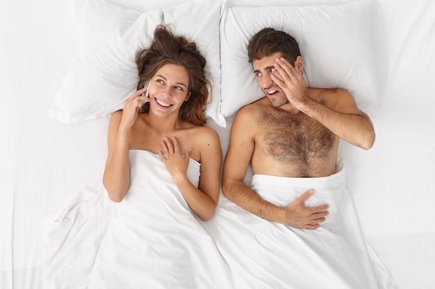 Spraakzame vrouw heeft telefoongesprek via moderne mobiele telefoon, let niet op echtgenoot die geïrriteerd en verveeld in bed ligt, communicatie nodig heeft. mensen, technologieverslaving, relatieconcept
