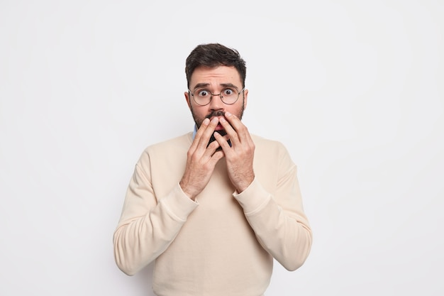 Sprakeloos bange man kijkt met schrik, trilt van angst houdt handen op mond draagt ronde bril en trui