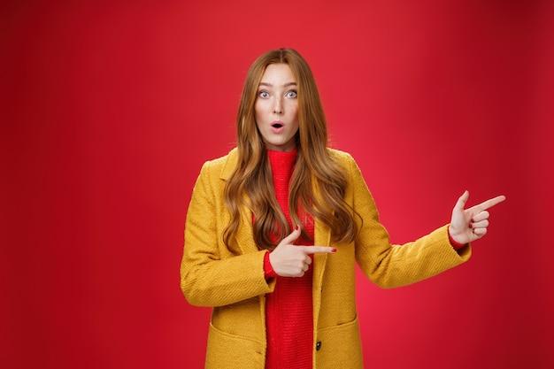 Sprakeloos ondervraagd en verward verrast roodharig meisje in gele herfstjas wijzend naar rechts...