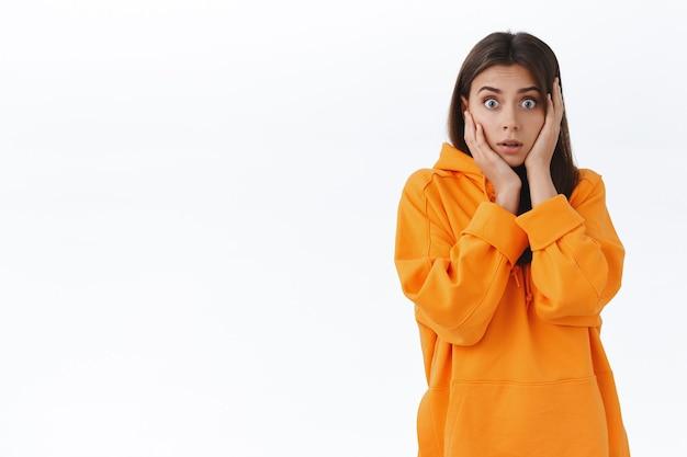 Sprakeloos verrast en bezorgd meisje hijgend staar camera geschrokken, pak hoofd open mond, hoor schokkend ongelooflijk nieuws, staande in oranje hoodie bezorgd over geruchten, witte muur