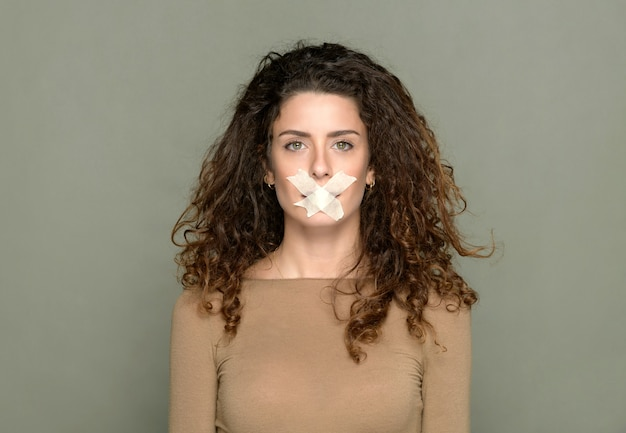 Sprakeloos vrouwtje met kruisvormige tape die de mond bedekt op een grijze achtergrond in de studio en naar de camera kijkt terwijl ze het stilteconcept toont
