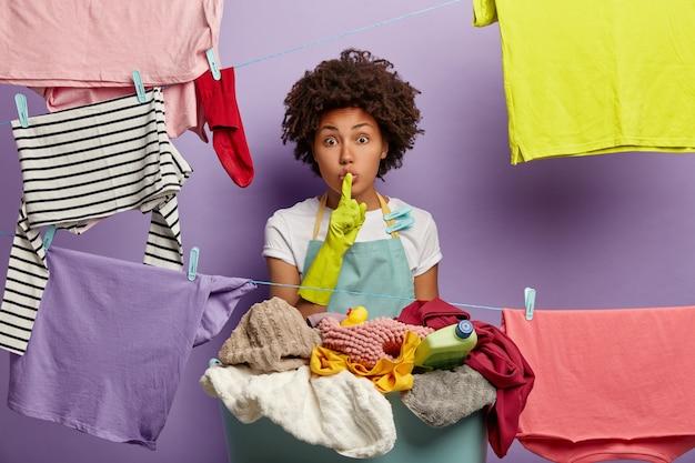 Sprakeloze jonge vrouw met een afro poseren met wasgoed in overall