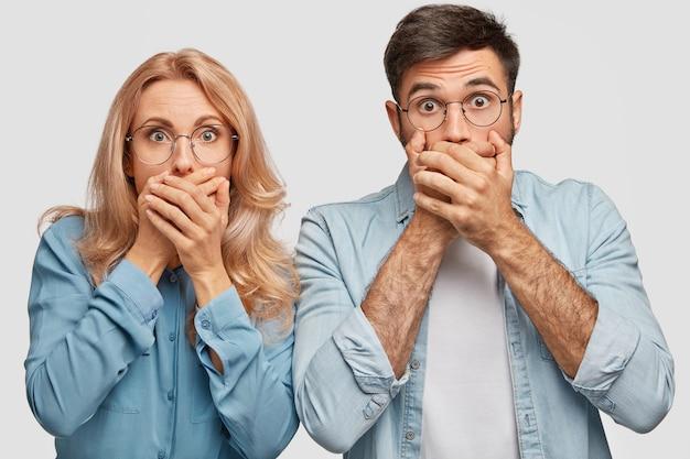 Sprakeloze mooie blonde vrouw en knappe man bedekken hun mond, bang om iets vreselijks te zien