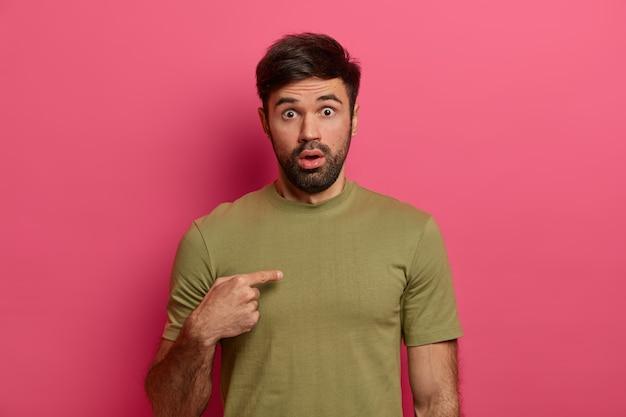 Sprakeloze verbaasde jongeman wijst met geschokte uitdrukking naar zichzelf, verbaasd waarom vriend hem de schuld geeft, wijst naar de borst, ogen afgeluisterd, draagt vrijetijdskleding, poseert over roze muur
