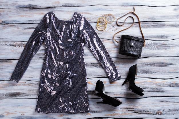 Sprankelende jurk met zwarte hakschoenen met lange mouwen en handtas avondoutfit idee voor glamoureuze meisjes...