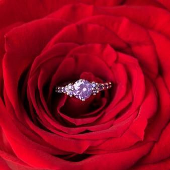 Sprankelende verlovingsring in rode roos. romantisch cadeau voor valentijnsdag. aanzoek concept.