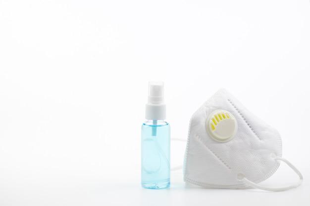Spray alcohol en medisch gezichtsmasker op een witte achtergrond die een ademhalingsmiddel zijn