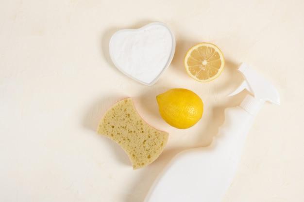 Spray fles, spons, citroen en frisdrank op beige backgrund top vire kopie ruimte schotel met zuiveringszout. niet giftig wasmiddel voor reiniging