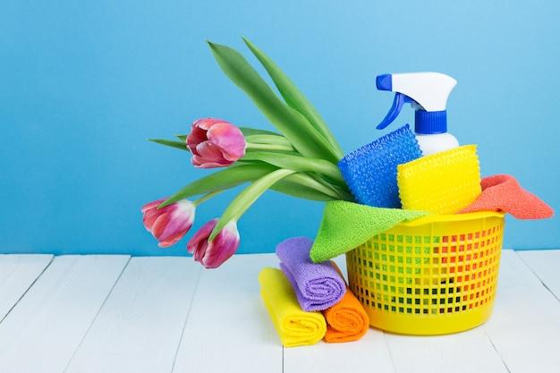 Spray met wasmiddel, schoonmaaksponzen, poetslappen en lentebloemen in de mand