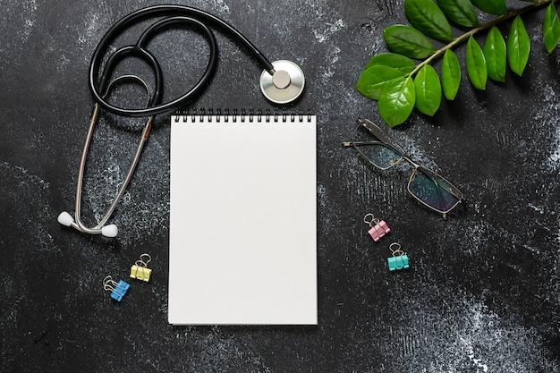 Spreekkamerconcept met lege blocnote, medische stethoscoop, glazen en groene installatie op de zwarte houten mening van de lijstbovenkant.