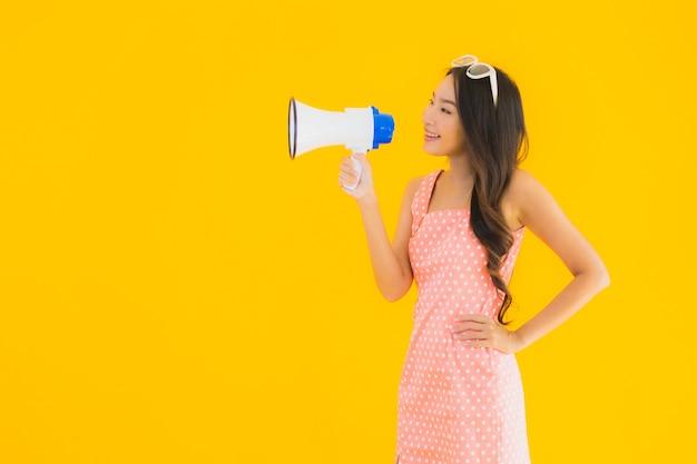 Spreekt de portret mooie jonge aziatische vrouw luid met megafoon