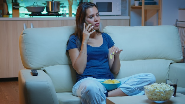 Spreken aan de telefoon met een kom met snacks en snacks eten voor de tv. gelukkige, ontspannen, eenzame dame in pyjama's genietend van de avond zittend op een comfortabele bank voor televisie met smartphone