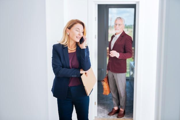 Spreken met de klant. blondharige makelaar in onroerend goed die elegant blauw kostuum draagt dat telefonisch met haar welvarende cliënt spreekt