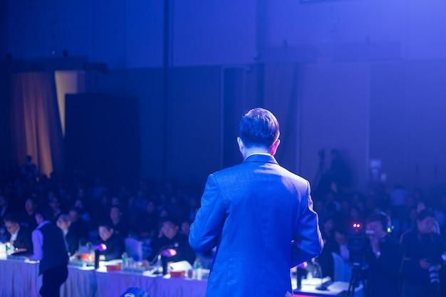 Spreker op stadium en het geven van bespreking op commerciële vergadering. publiek in de conferentiezaal.