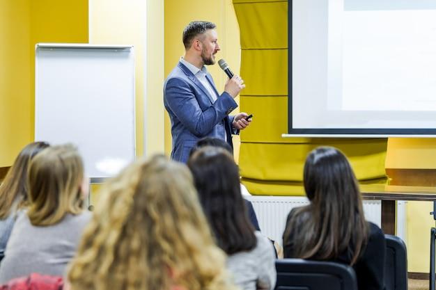 Spreker op zakelijke bijeenkomst. zakenman die afgevaardigden richt op conferentie