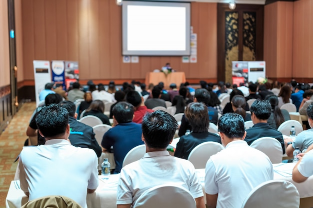 Sprekers op het podium met achteraanzicht van publiek in de conferentiezaal of seminarvergadering