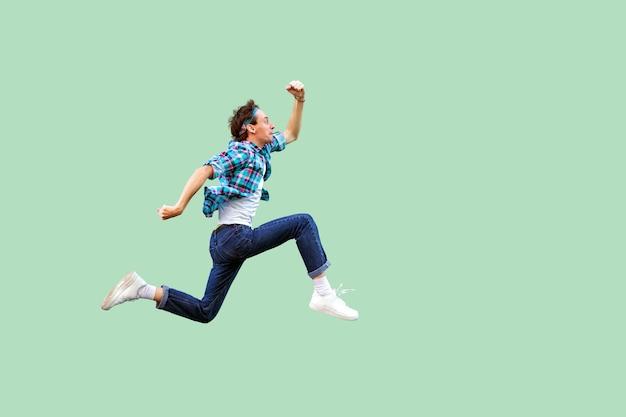 Spring naar het succes. zijaanzicht van het volledige profiel van een actieve jongeman in een casual blauw geruit hemd en een hoofdband die heel snel loopt of springt. indoor studio opname, geïsoleerd op groene achtergrond.