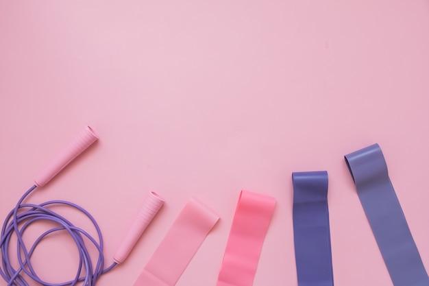Spring of springtouw en fitness elastiek op roze achtergrond. fitness trend.