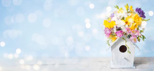Spring samenstelling, vogelhuisje met bloemen