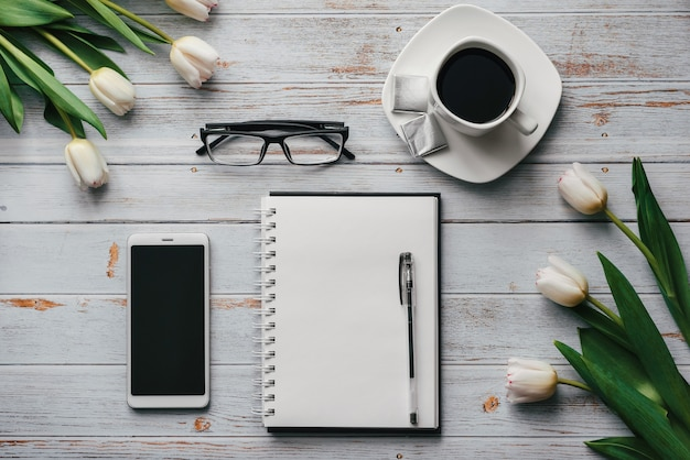 Spring spaties van de werkplek van een freelancer op met een boeket witte tulpen
