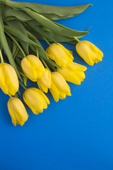 Spring tafel. gele tulpen op de blauwe tafel. bovenaanzicht. kopieer ruimte.