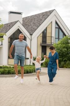 Springen en rennen. gelukkig stralende familie springen en rennen tijdens het wandelen in de avond