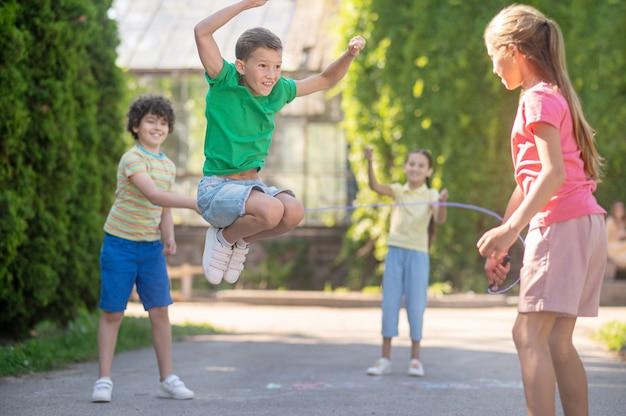 Springen. enthousiaste blonde jongen stuitert en vrolijke vrienden met springtouw in park op zonnige dag