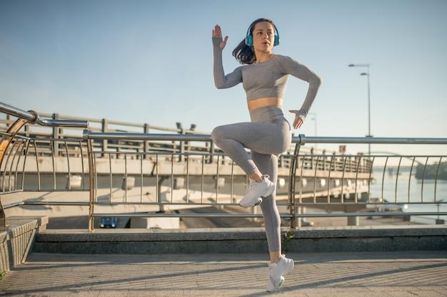 Springen. fit meisje in grijze sportkleding die springt tijdens haar opwarmingsoefening