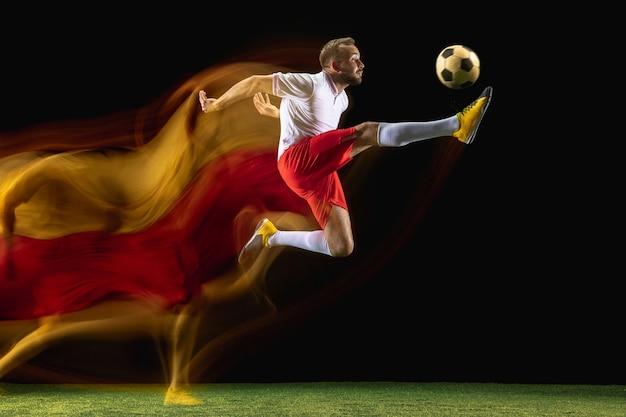 Springen. jonge blanke mannelijke voetbal of voetballer in sportkleding en laarzen die bal voor het doel schoppen in gemengd licht op donkere muur. concept van gezonde levensstijl, professionele sport, hobby.