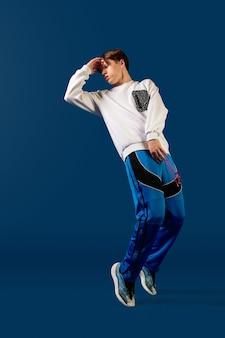 Springen. old-school ouderwetse jonge man dansen geïsoleerd op blauwe studio