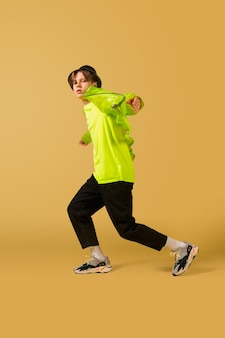 Springen. old-school ouderwetse jonge man dansen geïsoleerd op gele studio