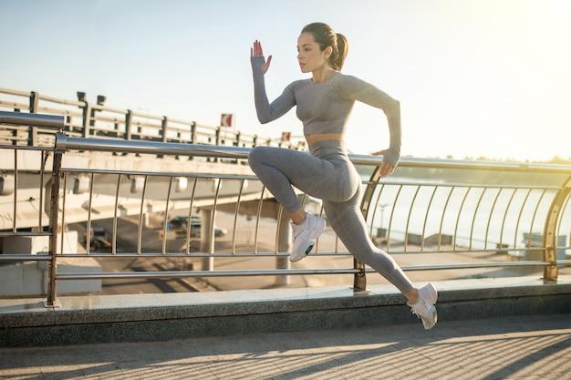 Springen. vrouwelijke sportpersoon in grijze sportkleding die tijdens haar opwarmingsoefening springt