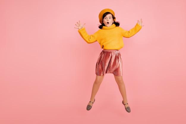 Springend meisje in gele trui. opgewonden kind dansen op roze muur.