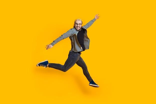 Springende blanke man met blond haar en bril luistert naar muziek op gele muur