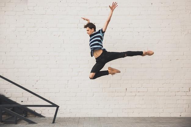 Springende jonge buinessman voor gebouwen, op de vlucht in sprong hoog